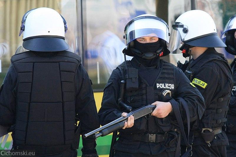 Policjant z bronią gładkolufową na wypadek rozrób